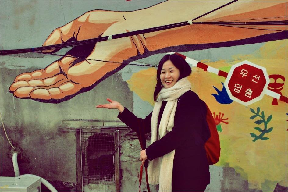 벽화그림 앞에서 포즈를 취하는 모습